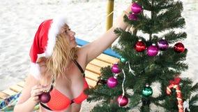 Junte al individuo y la muchacha en el sombrero de santa saludó el Año Nuevo y la Navidad en la playa Para adornar un árbol de na metrajes