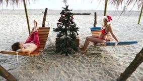 Junte al individuo y la muchacha en el sombrero de santa saludó el Año Nuevo y la Navidad en la playa Para adornar un árbol de na almacen de video