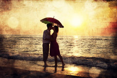 Junte besarse bajo el paraguas en la playa en puesta del sol. Foto en o Fotos de archivo