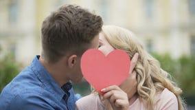Junte besarse, muchacha que pone encima del corazón de papel, gente joven en el amor, romántico almacen de video