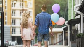 Junte caminar abajo de la calle que lleva a cabo las manos, individuo con los globos coloridos, romance Imágenes de archivo libres de regalías