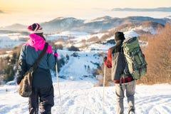 Junte caminar abajo de la montaña nevosa en tiempo de la puesta del sol Fotografía de archivo