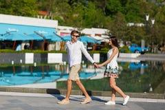 Junte caminar alrededor del centro turístico, celebrando las manos y la sonrisa fotos de archivo
