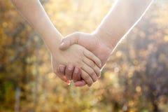 Junte caminar en el parque del otoño que lleva a cabo las manos Fotografía de archivo