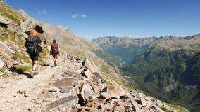 Junte caminar en el sendero en paisaje idílico de la montaña con el lago cristalino del agua, el pico de alta montaña y el glacia almacen de metraje de vídeo