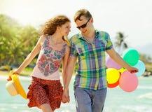 Junte caminar en la playa con las bolas coloreadas aire imágenes de archivo libres de regalías