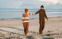 Junte caminar junto en el hombre y la mujer de la playa que llevan a cabo las manos imagen de archivo libre de regalías
