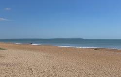 Junte caminar a lo largo de una playa abandonada en un día soleado Foto de archivo libre de regalías
