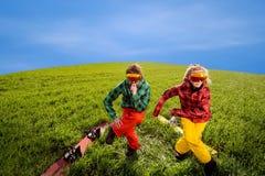 Junte divertirse en trajes de esquí con las snowboard en la hierba Imágenes de archivo libres de regalías