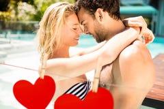 Junte el abarcamiento cerca de poolside contra los corazones que cuelgan en una línea Foto de archivo