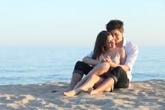 Junte el abarcamiento de sentarse en la arena de la playa Imagen de archivo