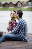 Junte el abarcamiento en el embarcadero mientras que muchacha que sostiene las flores amarillas Fotografía de archivo
