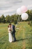 Junte el abarcamiento en prado en el día soleado con los globos Fotografía de archivo