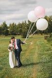 Junte el abarcamiento en prado verde con los globos grandes Foto de archivo libre de regalías