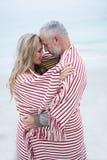 Junte el abarcamiento mientras que está envuelto en una toalla de playa Foto de archivo