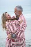 Junte el abarcamiento mientras que está envuelto en una toalla de playa Fotografía de archivo libre de regalías