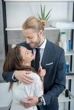 Junte el abarcamiento mientras que mujer que lleva a cabo la prueba de embarazo positiva en cuarto de baño Imagen de archivo