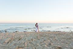 Junte el abarcamiento y besarse en la playa contra el océano Foto de archivo