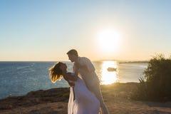 Junte el abarcamiento y besarse en la playa contra el océano Fotos de archivo