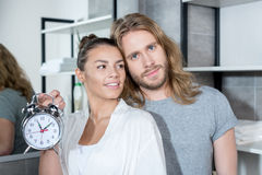Junte el abrazo mientras que mujer que sostiene el despertador en cuarto de baño Fotos de archivo libres de regalías