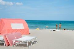 Junte el agua de la licencia que camina de nuevo a sus toallas en la playa mientras que p Fotografía de archivo libre de regalías