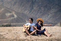 Junte el canto y tocar de la guitarra para comprar la playa foto de archivo