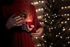 Junte el control y abra una caja de regalo roja de la Navidad con las luces mágicas fotos de archivo libres de regalías