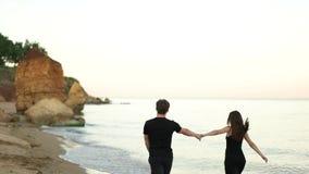 Junte el funcionamiento que celebra las manos descalzas en la playa almacen de video