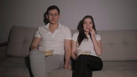 Junte el goce mirando una película en casa el reír en el sofá almacen de metraje de vídeo