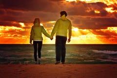 Junte el hombre y a la mujer en amor que caminan en la playa de la playa que se sostiene de común acuerdo Foto de archivo