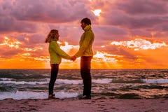 Junte el hombre y a la mujer en el amor que se coloca en la playa de la playa que lleva a cabo h Foto de archivo