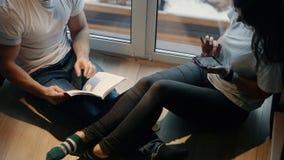 Junte el hombre y a la mujer para leer y para discutir el libro que se sienta en las escaleras por la ventana en la casa almacen de video