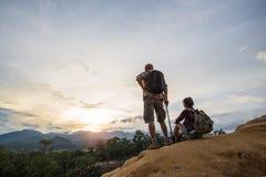 Junte el hombre y a la mujer que se sientan en el acantilado que goza de las montañas, viaje fotos de archivo