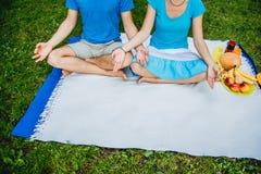 Junte el hombre y a la mujer que se sientan en el prado con la hierba verde en la posición de Lotus Medite en paz y la libertad imagen de archivo