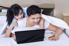 Junte el ordenador portátil del uso y la tarjeta de crédito en dormitorio Fotos de archivo libres de regalías