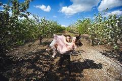 Junte el retrato de una muchacha y de un individuo que buscan un vestido de boda, un vuelo rosado del vestido con una guirnalda d Foto de archivo