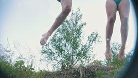 Junte el salto de un acantilado en el río el las vacaciones, cámara lenta metrajes