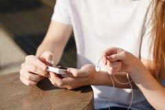 Junte escuchar la música con auriculares de botón de un teléfono elegante Fotos de archivo
