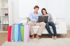 Junte hacer compras en línea con los bolsos en el sofá en casa Imágenes de archivo libres de regalías