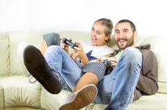 Junte jugar a los videojuegos que se divierten en el sofá Imagenes de archivo