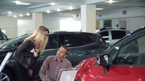 Junte la admiración de un coche rojo en una sala de exposición metrajes