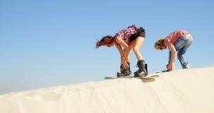 Junte la atadura de los tableros de la arena a las botas 4k metrajes
