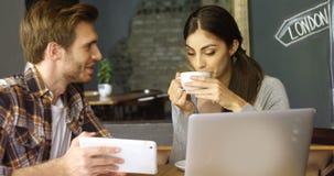 Junte la discusión sobre la tableta digital en el café 4k almacen de metraje de vídeo
