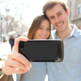 Junte la fabricación de una foto del selfie con un smartphone y mostrar la pantalla Imagen de archivo