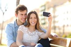 Junte la fotografía de un selfie con un teléfono elegante en un parque Fotografía de archivo libre de regalías