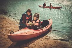 Junte la lectura de un mapa en kajaks en una playa foto de archivo