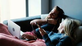 Junte la música que escucha en el teléfono móvil mientras que usa el ordenador portátil en la sala de estar 4k metrajes