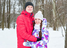Junte la mirada de la cámara con sonrisas en parque del invierno Imagenes de archivo