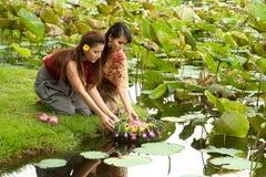 Junte a la mujer bonita tailandesa en vigueta flotante de la flor. imagenes de archivo