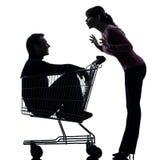 Junte a la mujer con el hombre que se sienta en silueta del carro de la compra Imagen de archivo